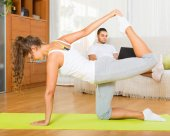 Girl doing yoga and man with laptop — Stock Photo