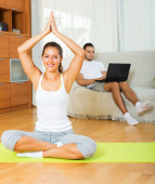 Female in yoga position and lazy guy on sofa   — Stockfoto