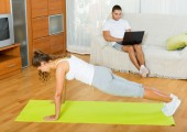 Girl practicing fitness and boyfriend resting with laptop   — Stockfoto