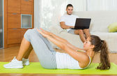 Girl practicing fitness and boyfriend resting   — Stockfoto