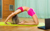 Female doing yoga with laptop — Stock Photo