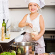 Happy baby girl in cook hat cooking soup — Stock Photo #59519701