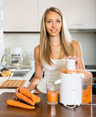 Girl making carrot juice — Stock Photo