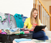woman sitting  near suitcase while using digital tablet — Stock Photo