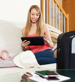 Girl sitting on sofa near luggage — Stock Photo
