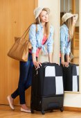 Woman in hat with a suitcase going on holidays — Stock Photo