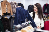 Woman choosing jacket at store — Stock Photo