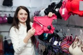 female buyer choosing bra at clothing shop — Stock Photo