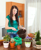 Woman transplanting flowers  in flowerpot — Stock Photo