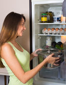 Woman near refrigerator — Stock Photo