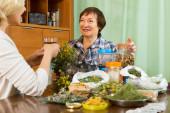 Two women brewing herbal tea — Stock Photo