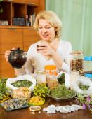 Mature woman brewing herbs  — Stock Photo