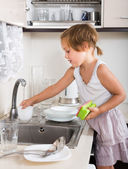 Small child cleaning dishes — Stok fotoğraf