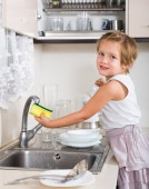 Cute little girl cleaning dishes  — Stock Photo