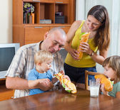 Family of four at lunch — Stock Photo