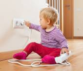 Toddler playing with extension cord and  electric outlet   — Stock Photo