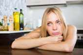 Sad young woman sitting at kitchen — Stockfoto