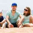 Parents with boy sitting on the sea sand — Stock Photo #59531083