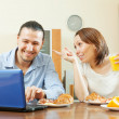 Happy couple looking e-mail in laptop during breakfast — Stock Photo #59533377