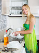 Woman washing plates with sponge — Stockfoto