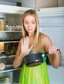 Woman holding foul food near fridge — Stock Photo
