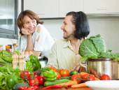 Charming couple preparing vegetable salad  — Stock Photo