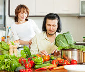 Happy couple cutting vegetables — Stock Photo