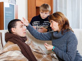 Woman and son caring for unwell man   — Stock Photo