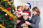 Parents with two children decorating Christmas tree   — Stock Photo