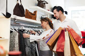Young couple choosing clothes at market — Stock Photo