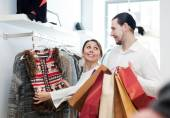 Couple choosing jacket at clothing shop — Stock Photo