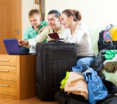 Three tourists packing luggage — Stock Photo