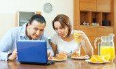 Ordinary couple looking e-mail in laptop during breakfast   — Stock Photo