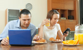 Couple using devices during breakfast   — Stock Photo