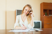 Smiling blonde woman fills in documents — Stock Photo