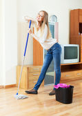 Positive long-haired girl washing parquet  with mop   — Foto de Stock