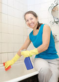 Smiling mature woman cleans bathroom   — Stock Photo