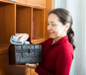 Woman wiping dust from wooden chest — Stok fotoğraf