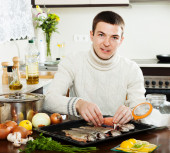 Handsome man salting fish on baking sheet — Stock Photo