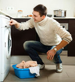 Man putting clothes into washing machine — Stock Photo
