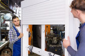 Workers  inspecting windows with shutter — Stockfoto