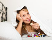 Woman with candy in bed — Stock Photo