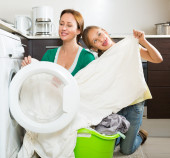 Woman with daughter  washing clothes — Stock Photo