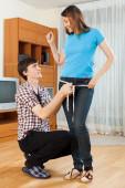 Guy measuring girlfriend — Stock Photo