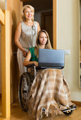 Girl in wheelchair  with  laptop — Stock Photo
