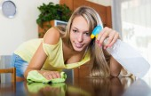 Woman dusting table — Stock Photo