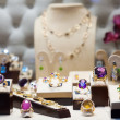Golden jewelry with gems at showcase  — Stock Photo #64253833