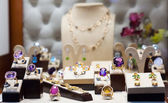 Golden jewelry with gems at showcase  — Stock Photo