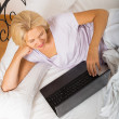 Mature woman with laptop in bed — Stock Photo #64280625
