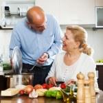 Mature couple cooking Spaniard tomatoes — Stock Photo #64282153
